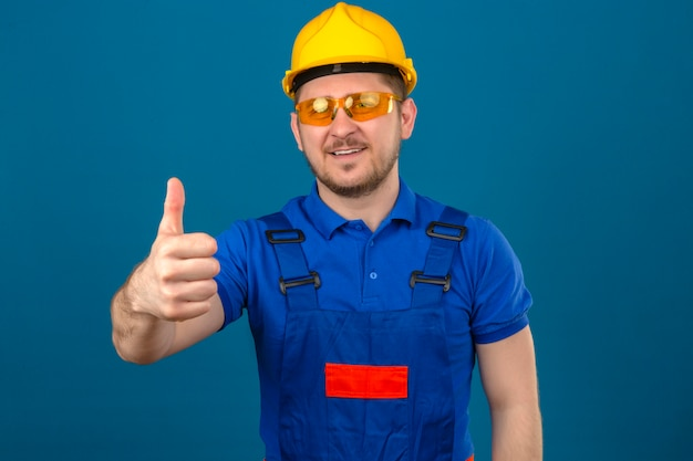 Baumeistermann, der bauuniformbrille und sicherheitshelm trägt, der freundlich lächelnd zeigt daumen oben über isolierter blauer wand