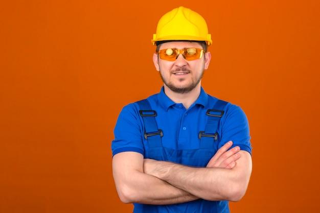Baumeistermann, der eine einheitliche baubrille und einen sicherheitshelm trägt, die mit den armen gekreuzt mit dem selbstbewussten lächeln über der isolierten orange wand stehen