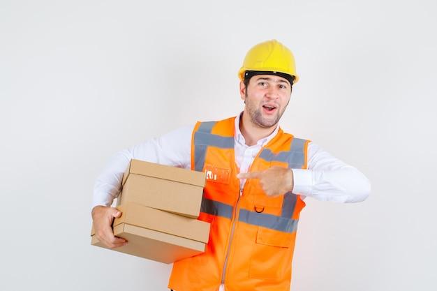 Baumeistermann, der finger auf pappkartons im hemd zeigt, uniform und positiv aussehend. vorderansicht.