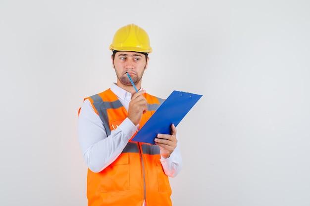 Baumeistermann, der klemmbrett und bleistift im hemd, uniform und hilflos aussehend hält. vorderansicht.