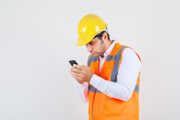 Baumeistermann, der smartphone in hemd, uniform und beschäftigt beschäftigt verwendet. vorderansicht.