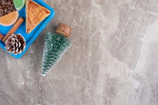 Baumfigur neben kyata-platte, zimtstange, marmelade und tannenzapfen auf marmor.