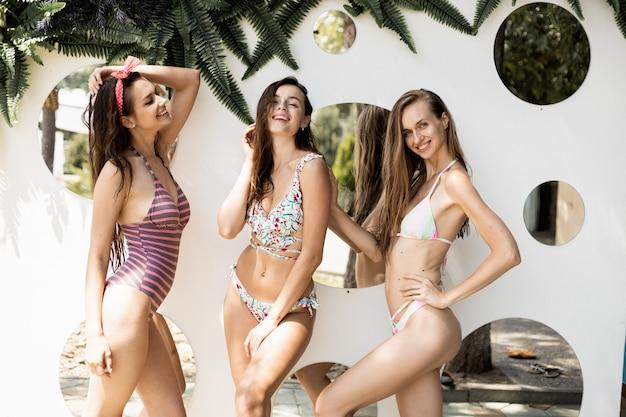 Baumschlanke schöne mädchen in badeanzügen posieren an einem sonnigen sommertag mit runden spiegeln im freien an der wand