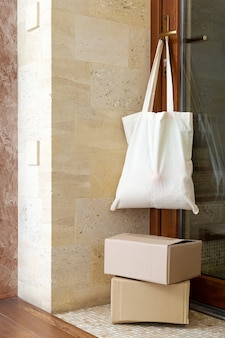 Baumwoll-einkaufstasche mit lebensmitteln am türgriff. kontaktlose lebensmittellieferung. lieferboxen auf der veranda in der nähe des hauses. sicheres einkaufen während der quarantäne von coronavirus covid 19. wohltätigkeitsspenden