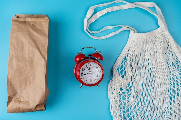 Baumwollbeutel, netzbeutel. papiertüte. zero-waste-konzept. umweltfreundlich. flache lage mit einem roten weckerbild