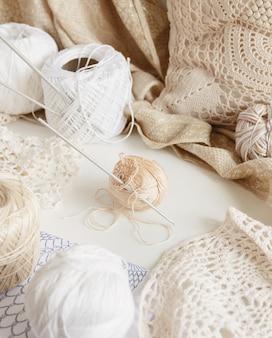 Baumwollfaden und haken auf einem tisch, umgeben von beigen und weißen wattebällchen