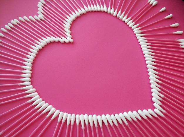 Baumwollknospen in form eines herzens auf einem rosa hintergrund ausgelegt.
