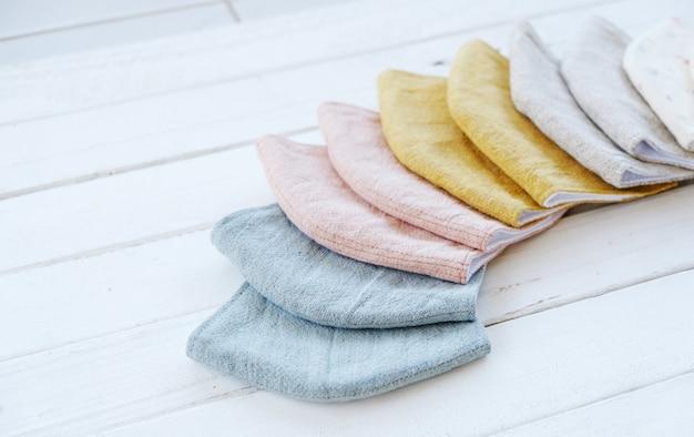 Baumwollmaske und musselin. wird zum schutz vor koronaviren verwendet. detaillierte nähte sind in den blumenmustern blau, gelb und rosa erhältlich.