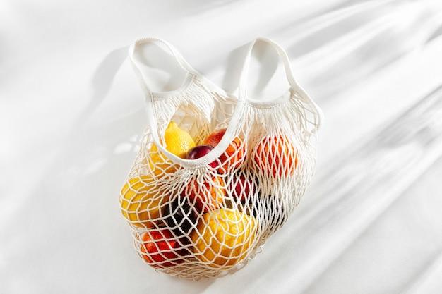 Baumwollnetzbeutel mit früchten. nachhaltiger lebensstil. umweltfreundliches konzept.