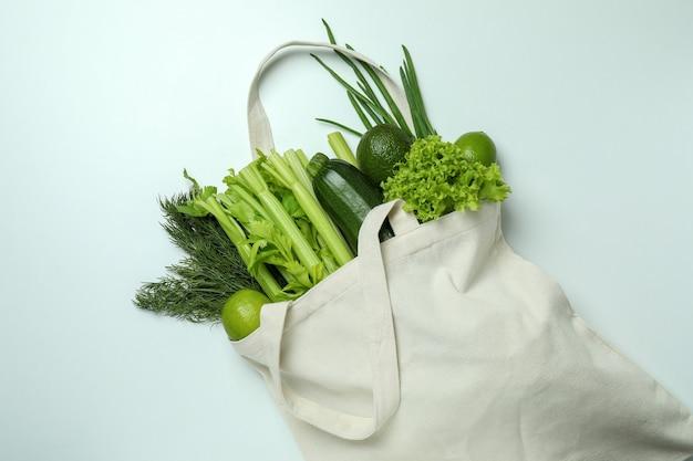 Baumwolltasche mit grünem gemüse auf weißem hintergrund