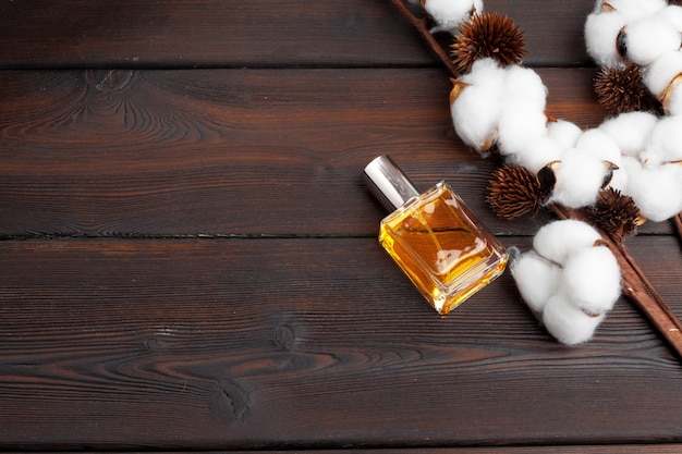 Baumwollzweig mit parfümflasche auf hölzernem hintergrund