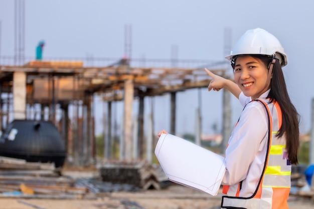 Bauplanarchitekt des bauingenieurs der asiatischen frau, der weißen sicherheitshelm trägt