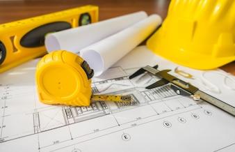 Baupläne mit gelben Helm und Zeichenwerkzeuge auf Bluep