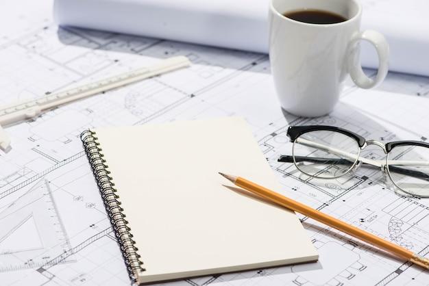 Bauprojekte. planung. öffne blaupausen mit bleistift und notizbuch.
