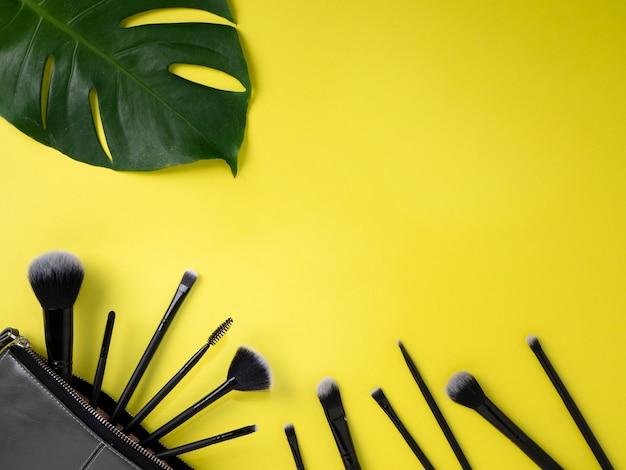 Bauschen sie sich mit make-upbürsten, kosmetik, gelbem hintergrund