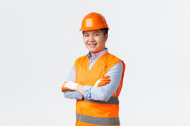 Bausektor und industriearbeiterkonzept. selbstbewusster junger asiatischer ingenieur, bauleiter in reflektierenden kleidern und helm, verschränkten armen und frech lächelnd, für qualität, weiße wand