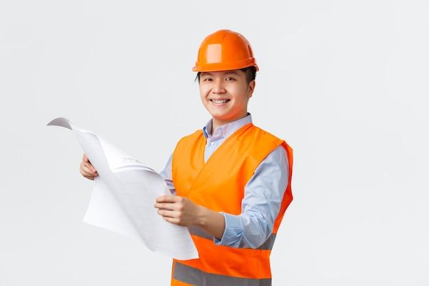 Bausektor und industriearbeiterkonzept. zuversichtlich lächelnder asiatischer architekt, chefingenieur im helm und in der reflektierenden jacke, die blaupausen hält, unternehmen inspizierend, weiße wand