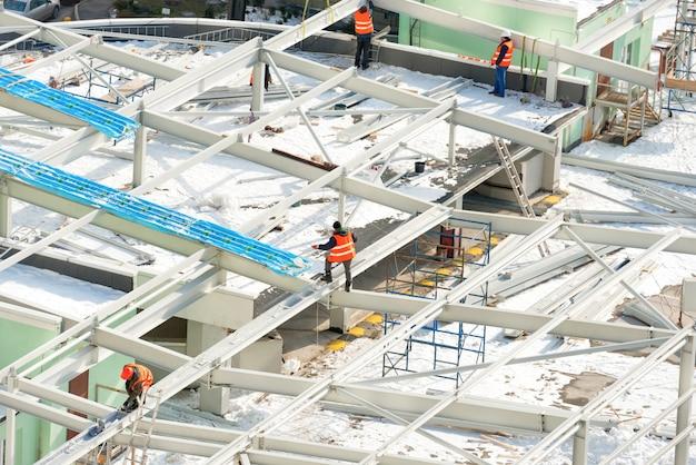 Baustelle mit arbeitern auf dem gebäudedach