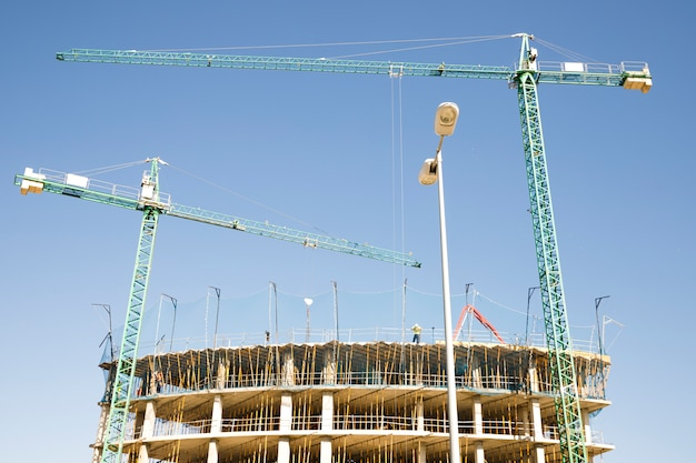 Baustelle mit kran und gebäude gegen blauen himmel