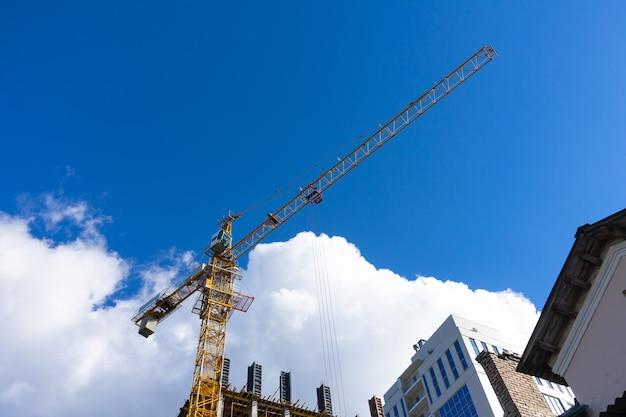 Baustelle mit turmdrehkran gegen blauen himmel