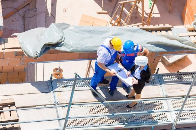 Baustelle team oder architekt und bauherr oder arbeiter mit helmen diskutieren auf einem gerüstbauplan oder bauplan oder checkliste