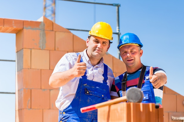 Baustellearbeitskräfte, die wände auf haus errichten