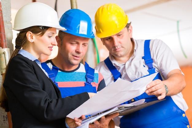 Baustellen-team oder architekt und bauunternehmer oder arbeiter mit helmen, die den plan oder die blaupause kontrollieren oder besprechen