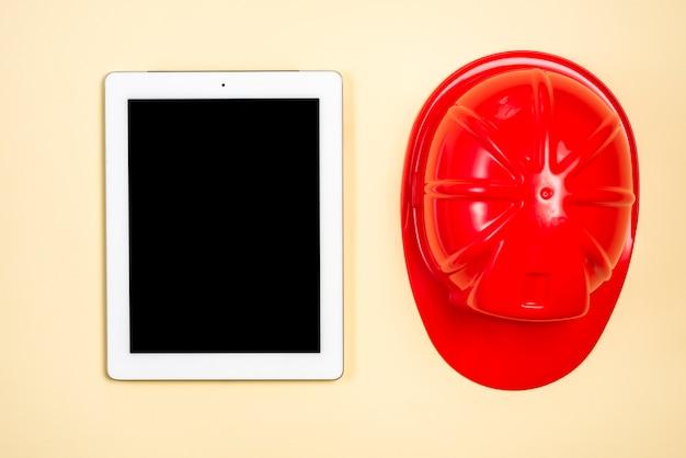 Bausturzhelm nahe der digitalen tablette mit anzeige des leeren bildschirms auf beige hintergrund