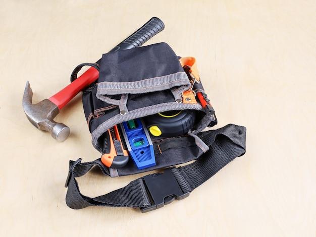Bautasche am gürtel für arbeitsgeräte auf sperrholz der oberfläche