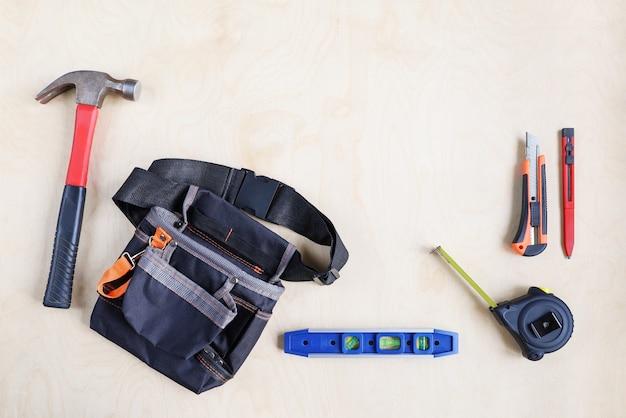 Bautasche für gürtel und einige arbeitsgeräte werkzeuge auf sperrholz der oberfläche