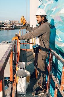 Bauunternehmer, bauunternehmer in großer höhe in einer bauwiege, drückt einen knopf, um aus der höhe auf den boden zu klopfen