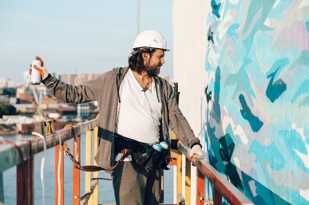 Bauunternehmer, künstler in großer höhe in einer gebäudewiege führt fassadenmalerei durch