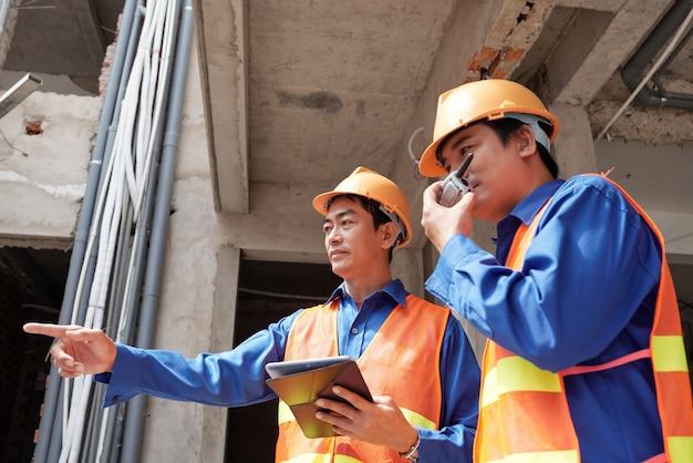 Bauunternehmer mit tablet-computer, die walkie-talkie verwenden, um die arbeit der bauherren auf der baustelle zu kontrollieren