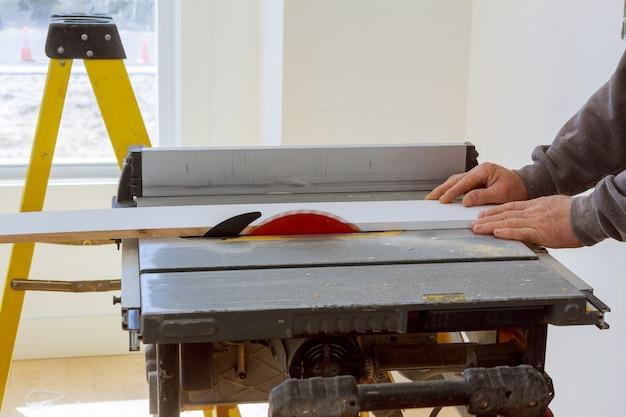 Bauunternehmerarbeitskraft, die kreissäge verwendet, um bretter auf einem neuen wohnungsbauprojekt zu schneiden