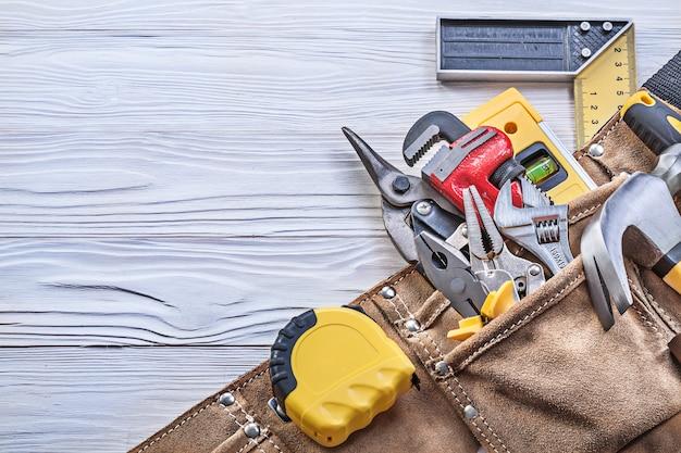 Bauwerkzeug im werkzeuggürtel auf holzbrettkonstruktionskonzept.