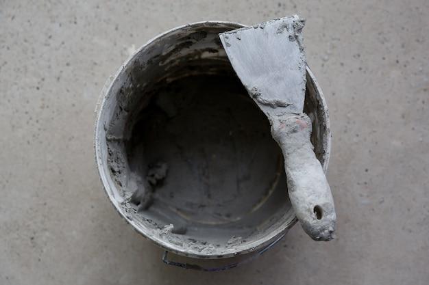 Bauwerkzeug spachtel in grauem kitt auf eimer