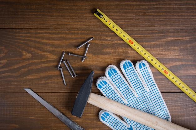 Bauwerkzeuge. hammer, nägel, metallsäge, messendes maßband und handschuhe auf einem hölzernen.