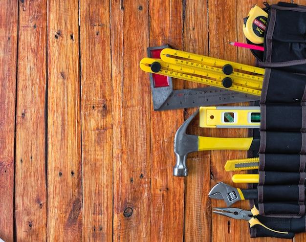 Bauwerkzeuge im werkzeuggürtel auf hölzernem hintergrund