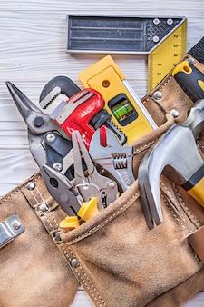 Bauwerkzeuge im werkzeuggürtel auf holzbrettkonstruktionskonzept