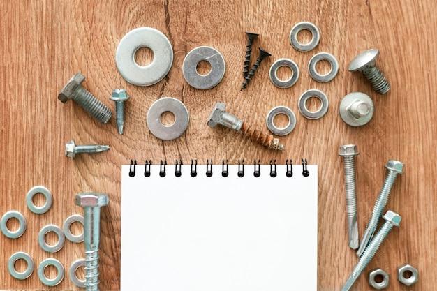 Bauwerkzeuge. schrauben, muttern und bolzen angeordnet um leeres spiralgebundenes notizbuchpapier auf hölzernem hintergrund. reparatur, heimwerkerkonzept.
