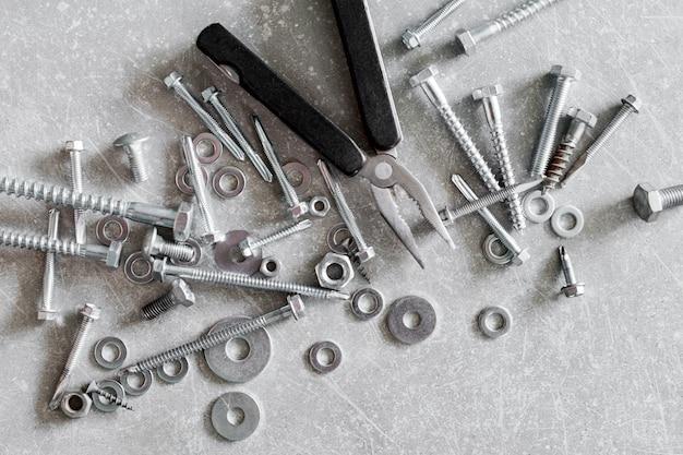 Bauwerkzeuge. schrauben, muttern und bolzen mit einer zange auf beton. reparatur, heimwerkerkonzept, draufsicht, flachlage.