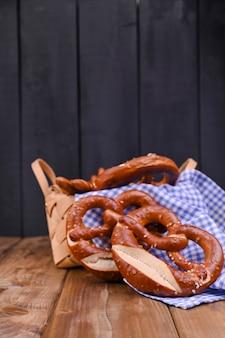 Bayerische brezel verziert mit einem blauen und weißen stoff auf einem rustikalen hölzernen brett münchen oktoberfest