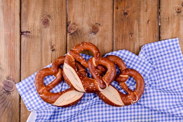 Bayerische brezel verziert mit einem blauen und weißen stoff auf einem rustikalen hölzernen brett