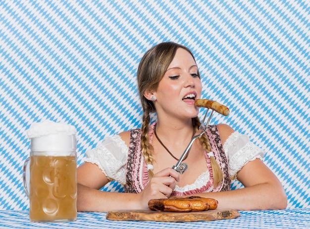 Bayerische frau, die deutsche bratwurst schmeckt