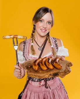 Bayerische frau, die traditionelles lebensmittel hält