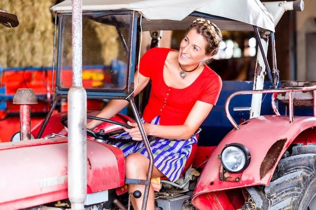 Bayerische frau mit dirndlkleid, das traktor fährt