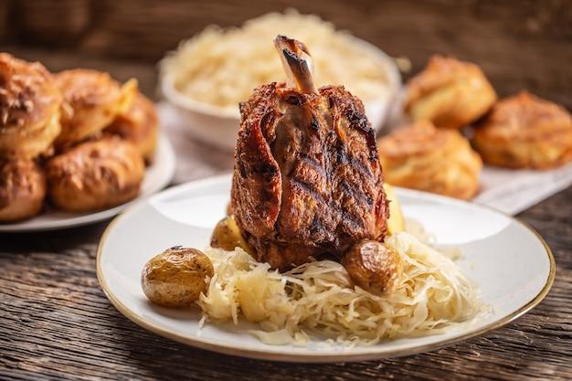 Bayerische schweinshaxe mit sauerkraut und ofenkartoffeln.