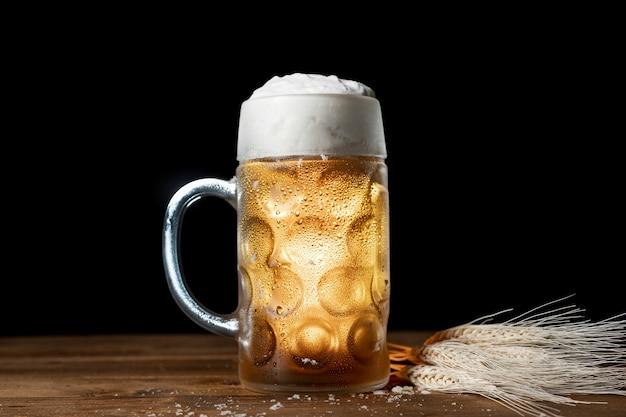 Bayerisches bier der nahaufnahme mit schaum auf einer tabelle