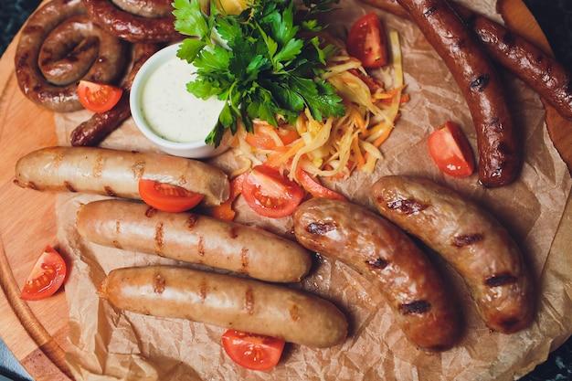 Bayerisches kalbfleischwurstfrühstück mit würstchen, weicher brezel und mildem senf auf holzbrett aus deutschland.