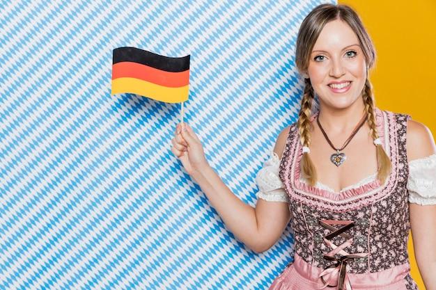 Bayerisches mädchen, das deutsche flagge hält